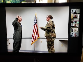 Capt. Tyler Relph, 932nd Medical Squadron critical care nurse, is sworn-in to active duty by Maj. Emily Derry, 932nd MDS Critical Care Flight commander, June 13, 2020 Scott Air Force Base, Illinois, as family and friends watch Relph's virtual ceremony via Zoom. (U.S. Air Force photo by Master Sgt. Christopher Parr)