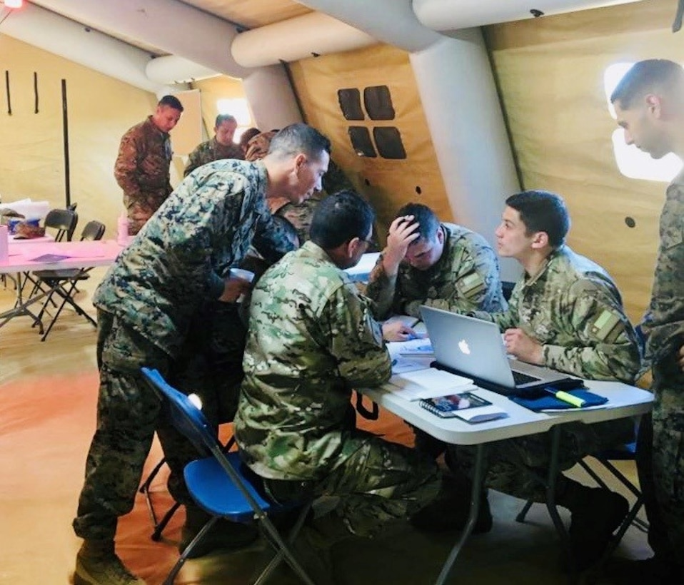 GySgt Alfonzo, LATAM Foreign Area SNCO, during an advisor mission with Chilean Marine Corps in Chile. GySgt Alfonzo explains Seabasing and other MEU Amphibious concepts to attentive Chilean Marine Corps Officers.