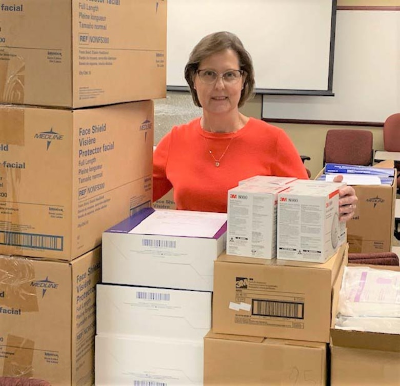 Photo of female Air Force Reservist standing behind boxes of personal protective equipment.