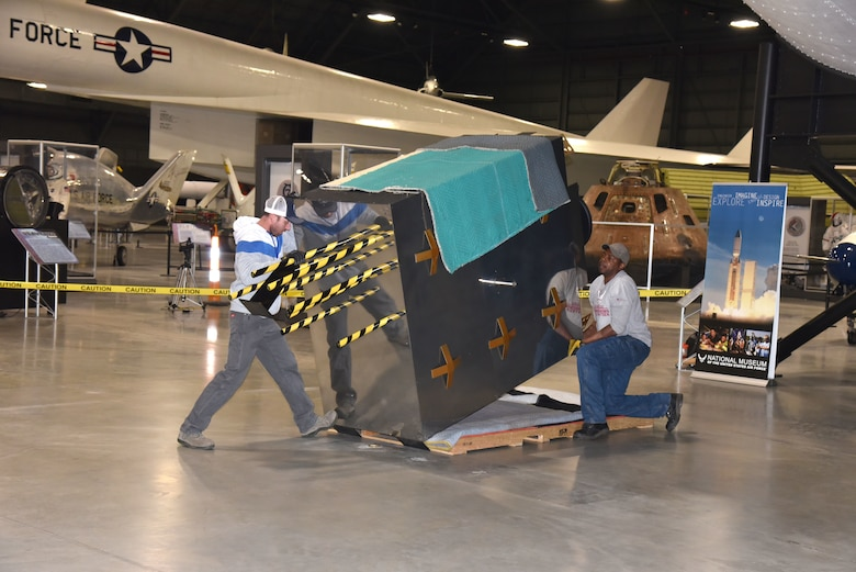 Museum exhibit specialists Taylor Burkhardt, left, and Quinton Johnson install the Global Positioning System (GPS) exhibit in the Space Gallery at the National Museum of the U.S. Air Force. (U.S. Air Force photo/Ken LaRock)