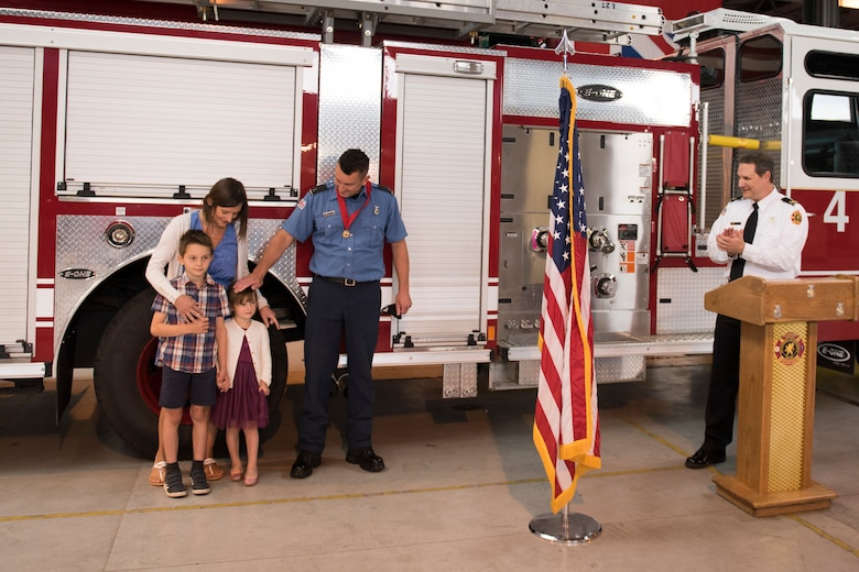 Lee Joyce, 423rd Civil Engineer Squadron lead firefighter, is awarded the Fire Department's Life Saving Medal at RAF Alconbury, England, June 16, 2020, for saving his daughter's life. Lee utilized his firefighter training to assist his four-year-old daughter when she was chocking on a chocolate egg May 16, 2020. (U.S. Air Force photo by Airman 1st Class Jennifer Zima)