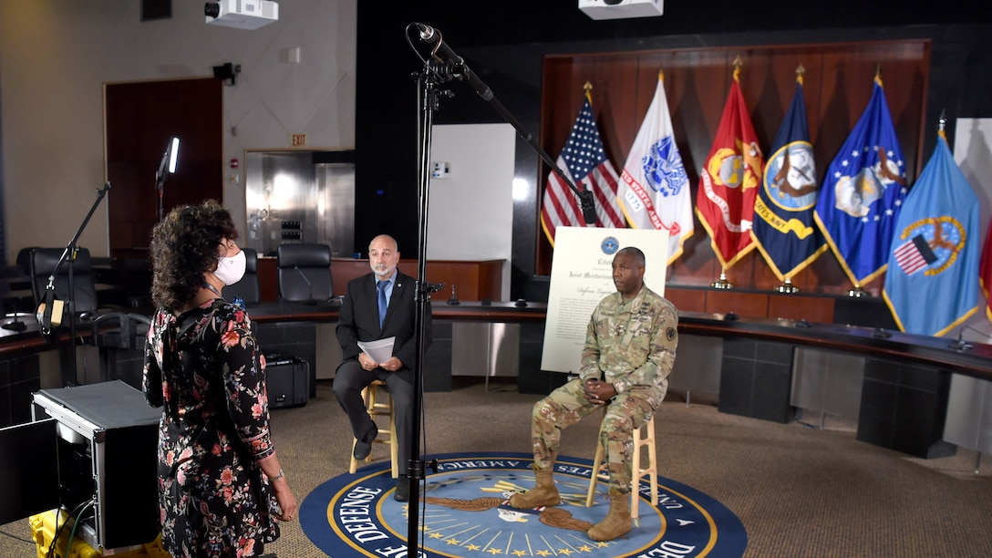 Two men - one white wearing a suit, the other black in an Army uniform - sit on stools with flags behind them as a woman in a white face mask stands in front of them. A tall, arching light illuminates the men.