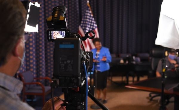 A black woman in a bright blue jacket sings in front of a camera with the U.S. flag behind her and studio lights shining on her.