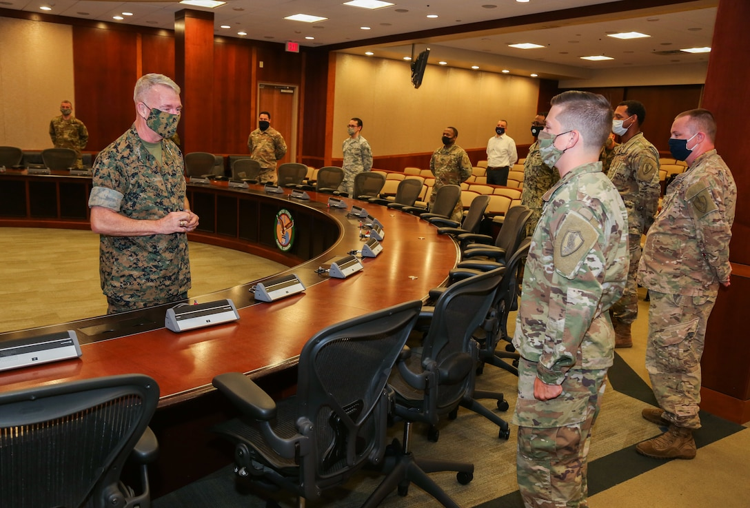 U.S. Marine Corps Gen. Kenneth F. McKenzie, commander, U.S. Central Command (USCENTCOM) presents a coin to a Soldier assigned to USCENTCOM's Command Center, using COVID-19 social distancing protocols, June 16, 2020. USCENTCOM's Command Center was awarded a U.S. Air Force Command and Control Operations Award for Service Watch/Command Center of the Year 2019. The team was evaluated in leadership and performance in mission execution, outside community involvement, and training program recognitions. (U.S. Central Command Public Affairs photo by Tom Gagnier)