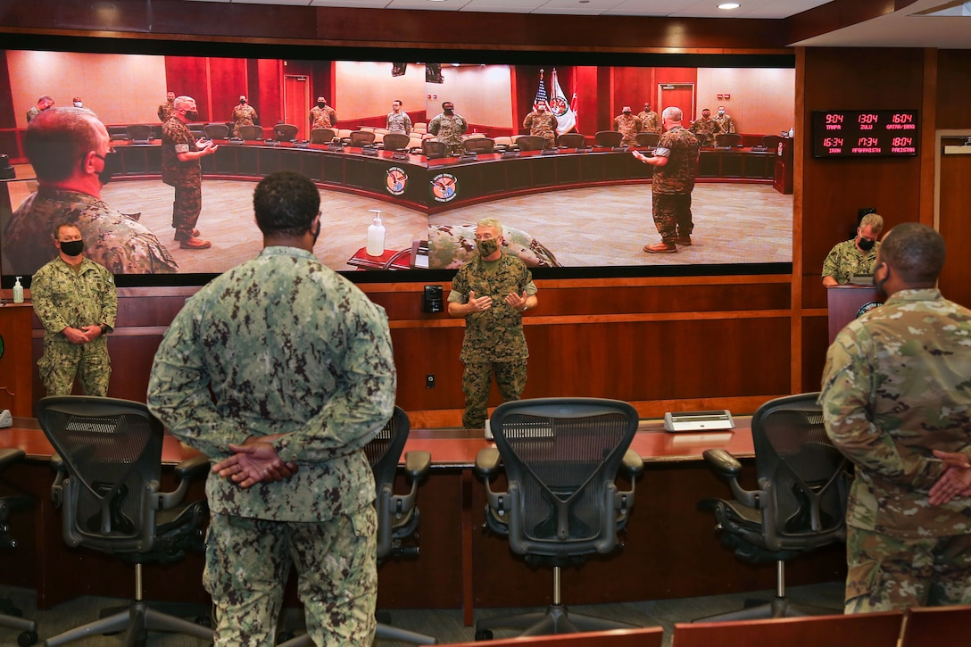 U.S. Marine Corps Gen. Kenneth F. McKenzie, commander, U.S. Central Command (USCENTCOM), center, and Fleet Master Chief James Herdel, senior enlisted leader, USCENTCOM, far left, address service members assigned to USCENTCOM's Command Center, using COVID-19 social distancing protocols, June 16, 2020. USCENTCOM's Command Center was awarded a U.S. Air Force Command and Control Operations Award for Service Watch/Command Center of the Year 2019. The team was evaluated in leadership and performance in mission execution, outside community involvement, and training program recognitions. (U.S. Central Command Public Affairs photo by Tom Gagnier)