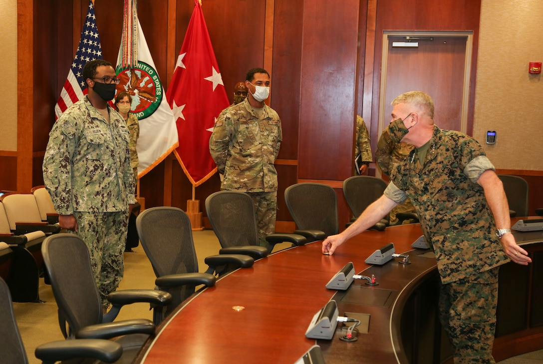 U.S. Marine Corps Gen. Kenneth F. McKenzie, commander, U.S. Central Command (USCENTCOM) presents a coin to a Sailor assigned to USCENTCOM's Command Center, using COVID-19 social distancing protocols, June 16, 2020. USCENTCOM's Command Center was awarded a U.S. Air Force Command and Control Operations Award for Service Watch/Command Center of the Year 2019. The team was evaluated in leadership and performance in mission execution, outside community involvement, and training program recognitions. (U.S. Central Command Public Affairs photo by Tom Gagnier)