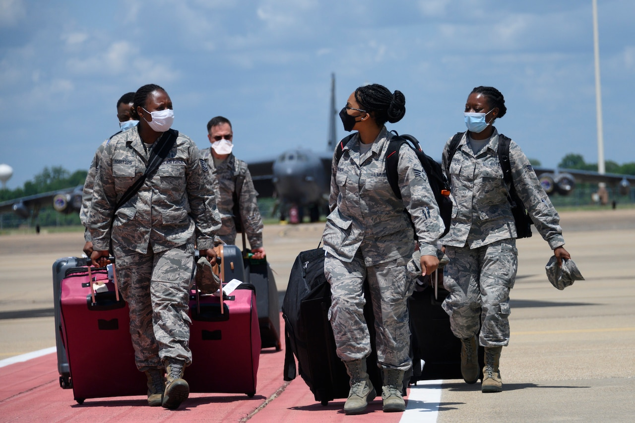 Airmen wearing face masks pull rolling suitcases while walking on a flight line.