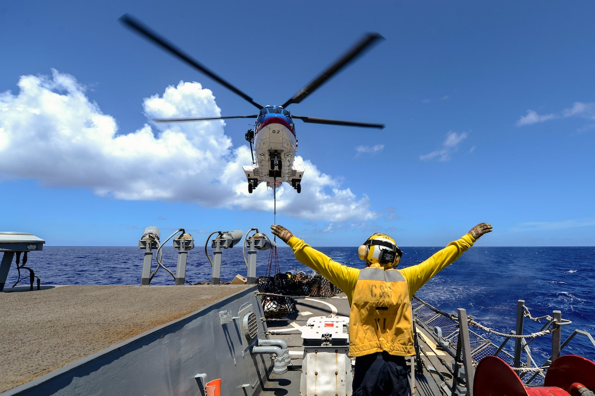 A sailor signals the pilot of a helicopter.