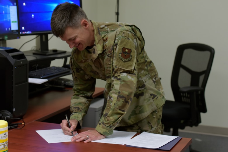 U.S. Air Force Col. Thomas Coakley, 17th Training Group commander, physically signs a Memorandum of Understanding, which creates the Center for Teaching and Learning Excellence for shared professional development between the San Angelo community and members of Goodfellow, during a video call conference in the Brandenburg Hall on Goodfellow Air Force Base, Texas, June 11, 2020. Per the National Defense Strategy, the facility's development was a multi-level collaboration to build lifelong learners. (U.S. Air Force photo by Senior Airman Zachary Chapman)