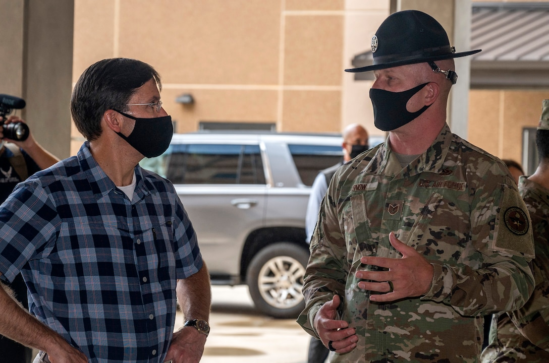 Tech. Sgt. Kenneth Snow, 323rd Training Squadron military training instructor, briefs U.S. Secretary of Defense Dr. Mark T. Esper during his tour of the 323rd Training Squadron's Airman Training Complex June 16, 2020, at Joint Base San Antonio-Lackland, Texas. Esper met with AETC leaders to see firsthand how Basic Military Training is fighting through COVID-19 with health protection measures in place and adapting operations to current Centers for Disease Control and Prevention Guidance. The visit also allowed him to witness how a citizen becomes an Airman during COVID-19.