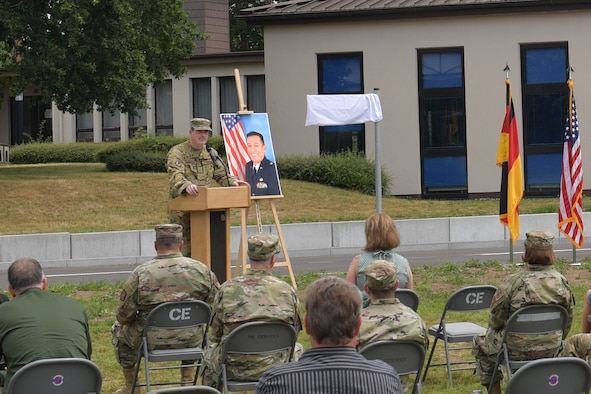 An Airman standing behind a podium in front of an audience.