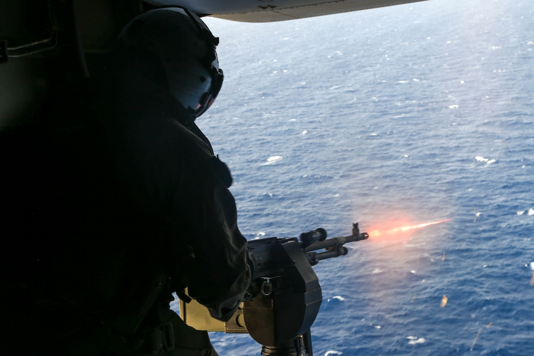 A U.S. Marine fires an M240B machine gun from an MV-22B Osprey in the Central Region, June 6.
