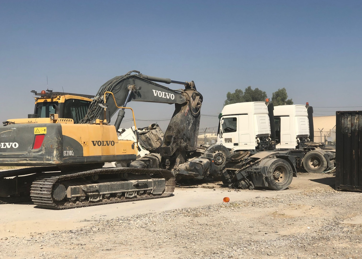 A heavy equipment operator uses shears to destroy one of the ten NATO bulk fuel carriers received at DLA Disposition Services' Kandahar site.