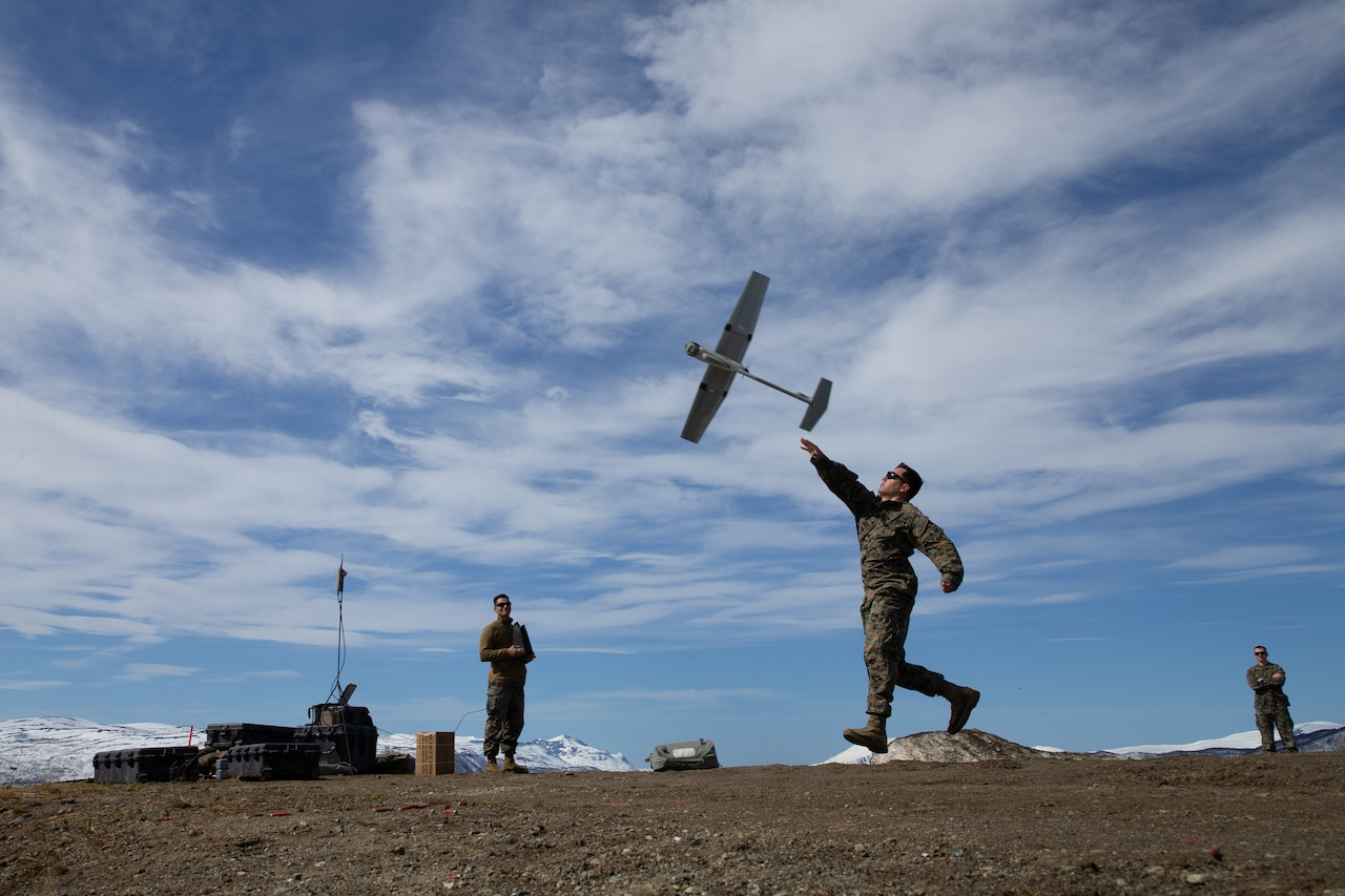 A service member launches a drone as two other service members watch from a distance.