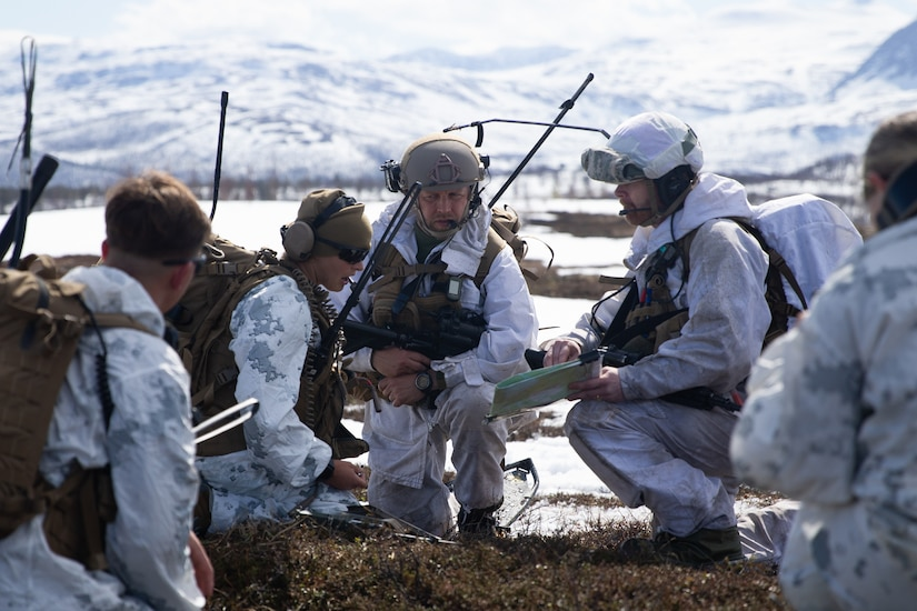 Service members wearing white uniforms kneel in a huddle to examine a map on snowy terrain.