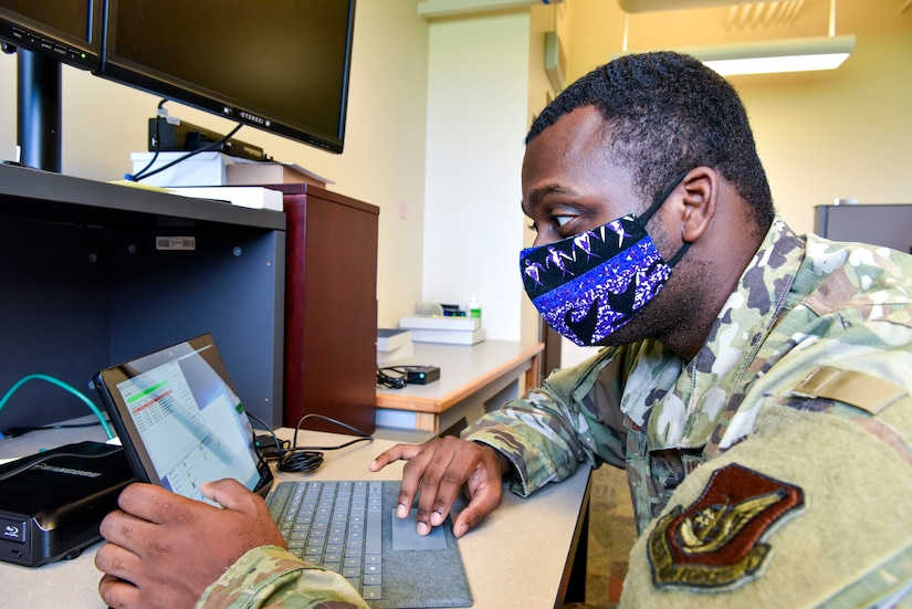 An airman wearing a face mask works on a computer.