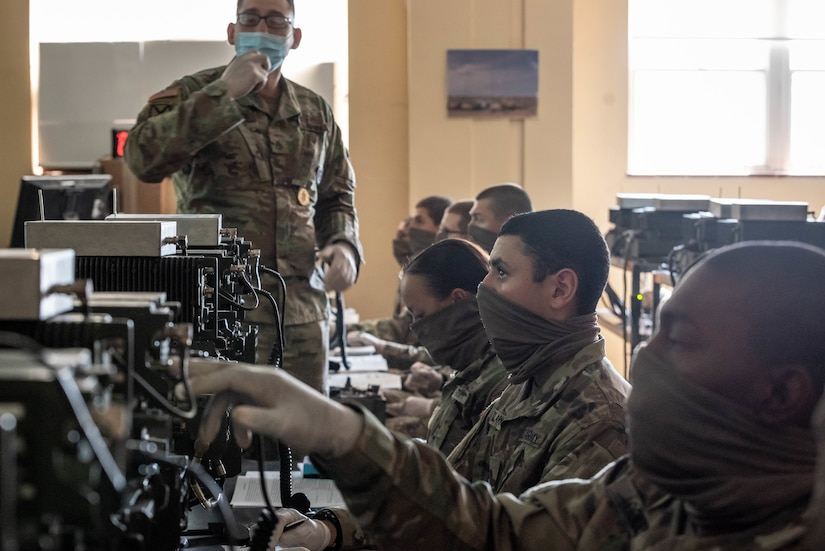 Seven service members wearing face masks sit in a row and operate radios as an instructor looks on.