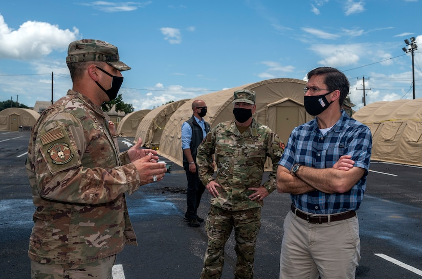An airman and a civilian talk in a tent city as another airman stands a safe distance between them. All are wearing face masks.