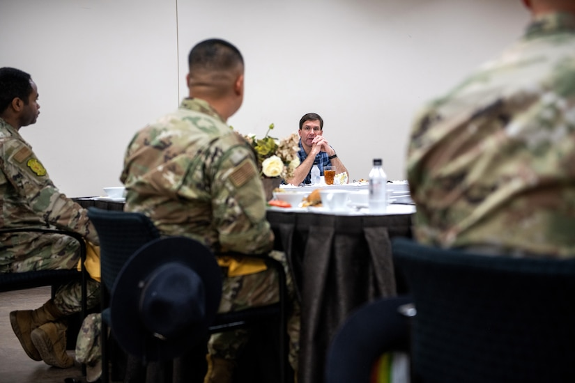 A civilian seated at a table talks with airmen during a working lunch.