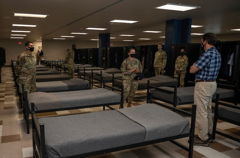 An airman briefs a civilian as basic trainees stand beside their bunks.