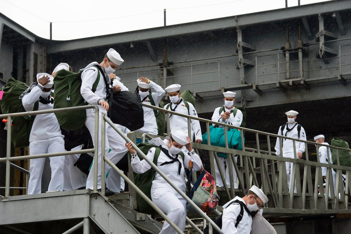 Sailors leave a ship wearing protective gear and carrying luggage.