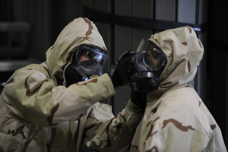 Tech. Sgt. Javier Mendoza, 940th Air Refueling Wing ground transport technician, and Staff Sgt. Jazmyn Sumrall-McCavley, 940th Logistics Readiness Squadron distribution operations technician, assist each other in securing the chemical, biological, radiological and nuclear overcoat hood to the M50 gas mask June 13, 2020, at Beale Air Force Base, California.