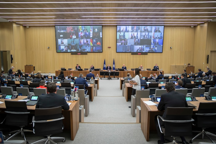 Screens display the faces of participants from around the world during a meeting as other participants practice social distancing in a large auditorium.