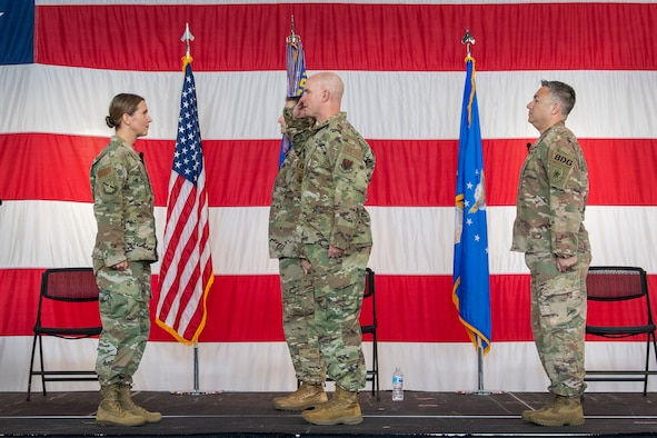 Group superintendent holds guidon during ceremony