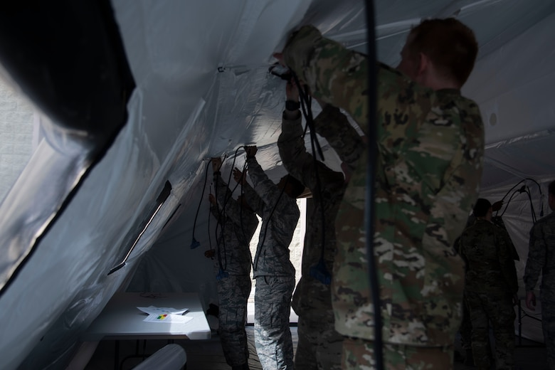366th Fighter Wing A2 (Intell) Airmen line the ceiling of the TM60 tent with power cables, June 3, 2020, on Mountain Home Air Force Base, Idaho,. A fully functional Agile Combat Employment Mission Planning Cell will include computers with full internet access and an heating ventalation and air conditioning system. (U.S. Air Force photo by Airman 1st Class Nicholas Swift)