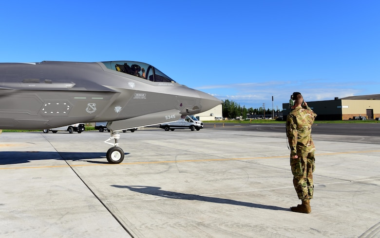 U.S. Air Force Lt. Col. Samuel Chipman, the 356th Fighter Squadron director of operations, returns a salute to Airman 1st Class Anthony Clark, a 356th Aircraft Maintenance Unit F-35A Lightning II crew chief, as he taxis to the runway at Eielson Air Force Base, Alaska, June 17, 2020.