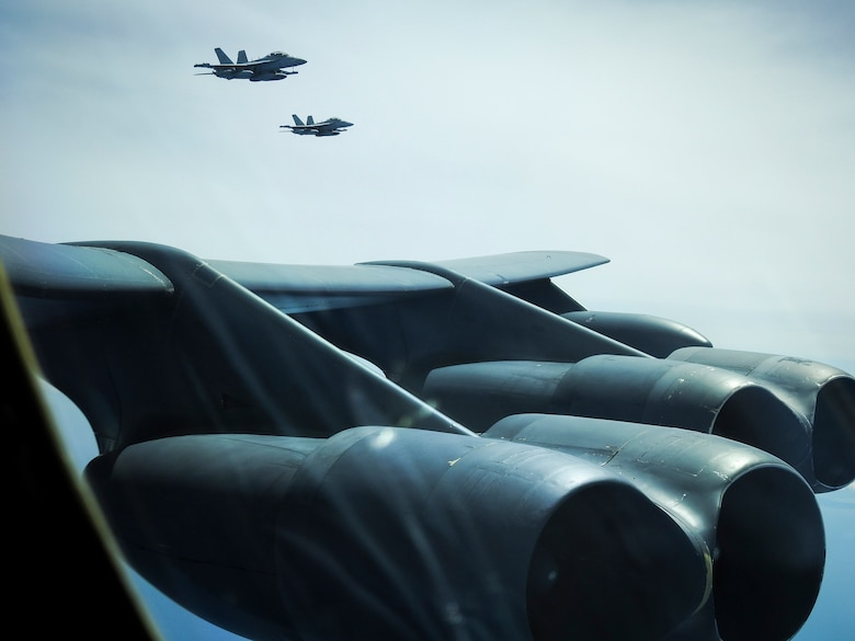 """Two United States Navy E/A-18G Growlers from Electronic Attack Squadron 209, the """"Star Warriors,"""" fly with a B-52H Stratofortress deployed from Barksdale Air Force Base, La., over the Sea of Japan while conducting a Bomber Task Force mission June 16, 2020. Strategic bomber missions contribute to joint force lethality, assure allies and partners, and deter aggression in the Indo-Pacific. (Courtesy photo)"""