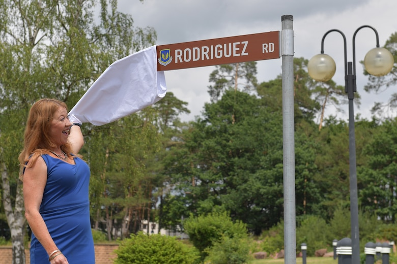 A person pulling a cloth cover off of a road sign.