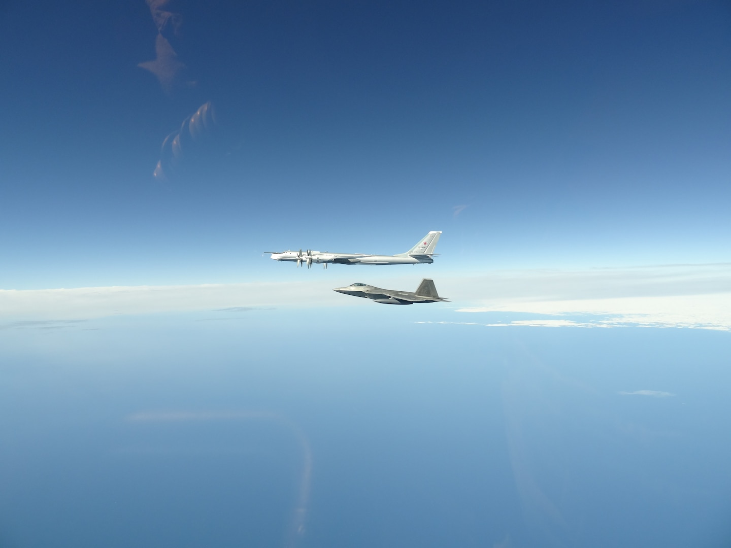 A North American Aerospace Defense Command F-22 Raptor flies next to a Russian Tu-95 bomber during an intercept in the Alaskan Air Defense Identification Zone June 16, 2020.