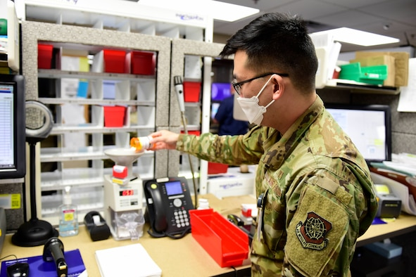 Image of an Airman pouring pills into a machine