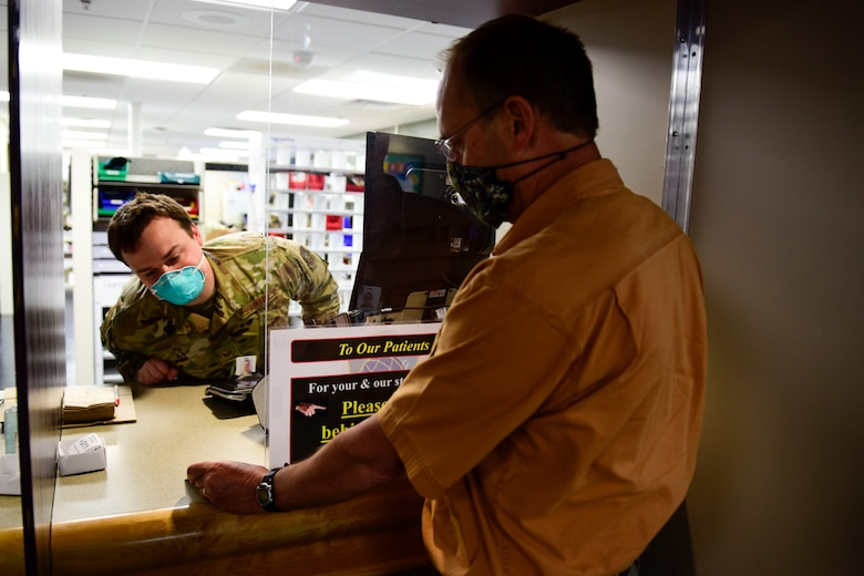 Staff Sgt. Sean Rourke (pictured left), 92nd Medical Support Squadron pharmacy technician, demonstrates a 'hands-off' approach for pharmacy technicians to verify a beneficiaries military identification card, May 29, 2020, at Fairchild Air Force Base, Wash. This verification technique, amongst other safety precautions, was put in place to aid in preventing the potential spread of the 2019 Coronavirus to keep pharmacy staff and patients safe. (U.S. Air Force photo by Staff Sgt. Nick J. Daniello)
