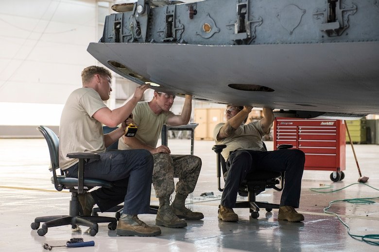 Tech Sgt. Daniel Barrow, Staff Sgt. Doug Miller and Staff Sgt. Kevin Cecil sit in office chairs, just the right height to comfortably repair damage to the cargo ramp on a C-17 Globemaster III aircraft at the 167th Airlift Wing, Martinsburg, W.Va., May 28, 2020.