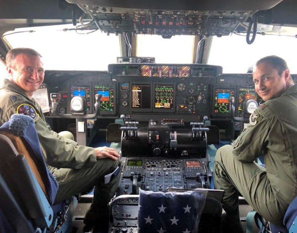 Photo shows two pilots in the cockpit of a C-5 aircraft.