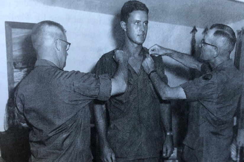 Three men participate in a promotion ceremony.