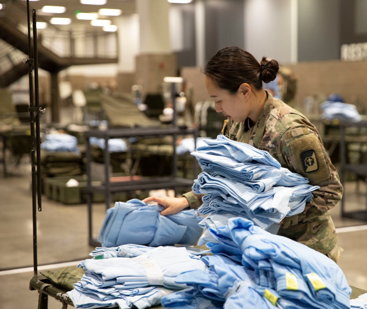 A female soldier wearing camouflage sorts through blue folded hospital gowns.