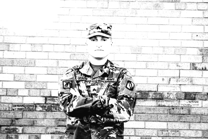 A soldier poses with his arms crossed over his chest in front of a brick wall.