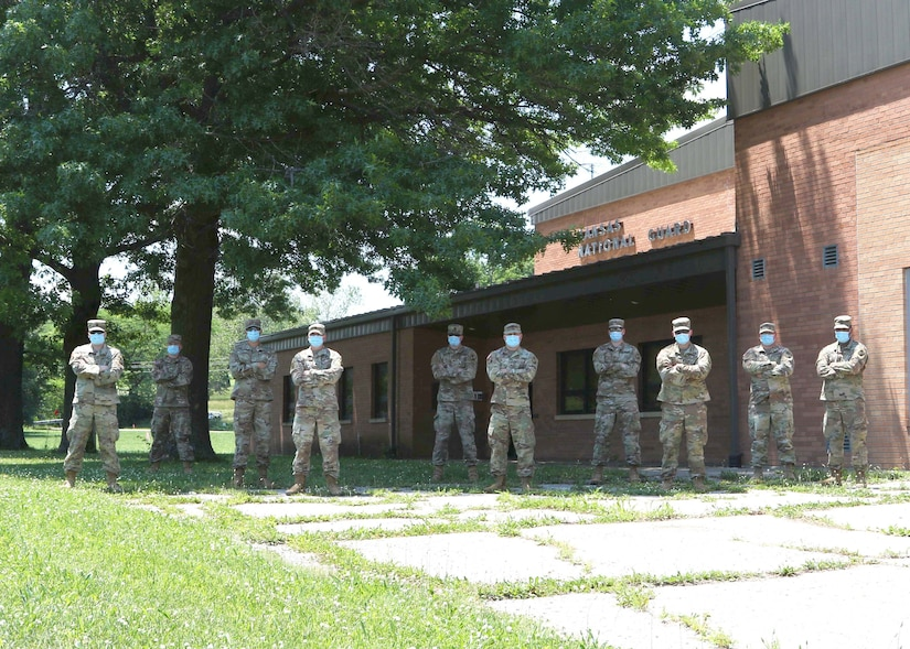 Ten soldiers with masks on stand in a yard in front of a building.