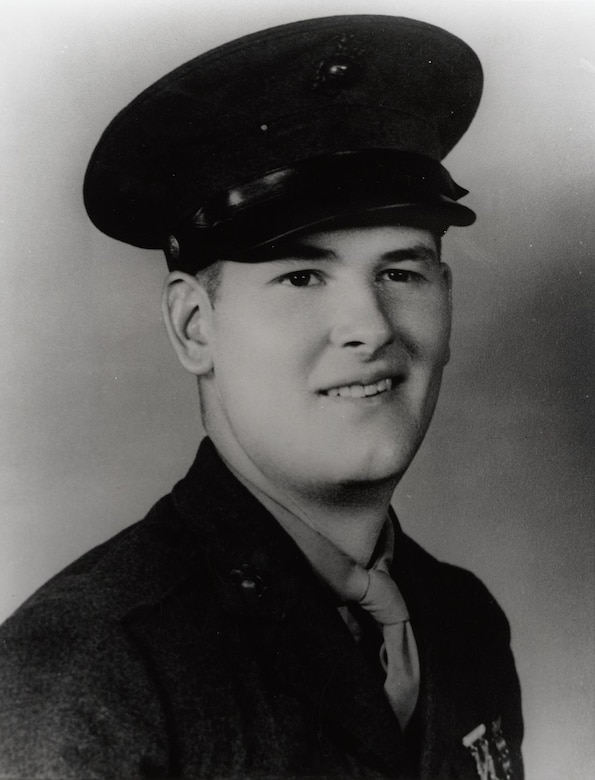 A man in a World War II uniform and cap smiles.