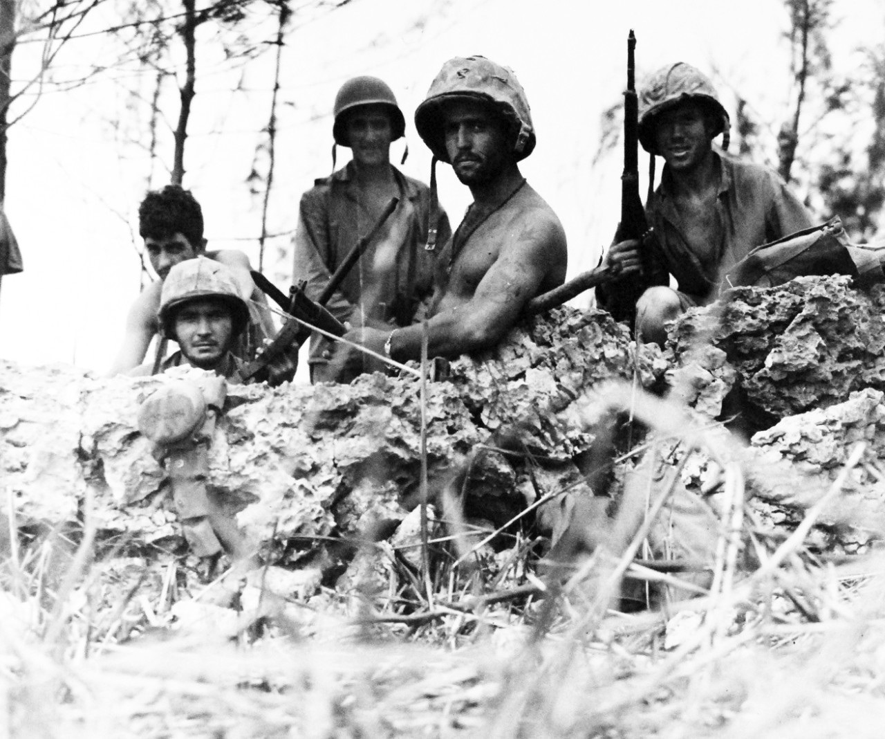 Five Marines in helmets stand in a hole.