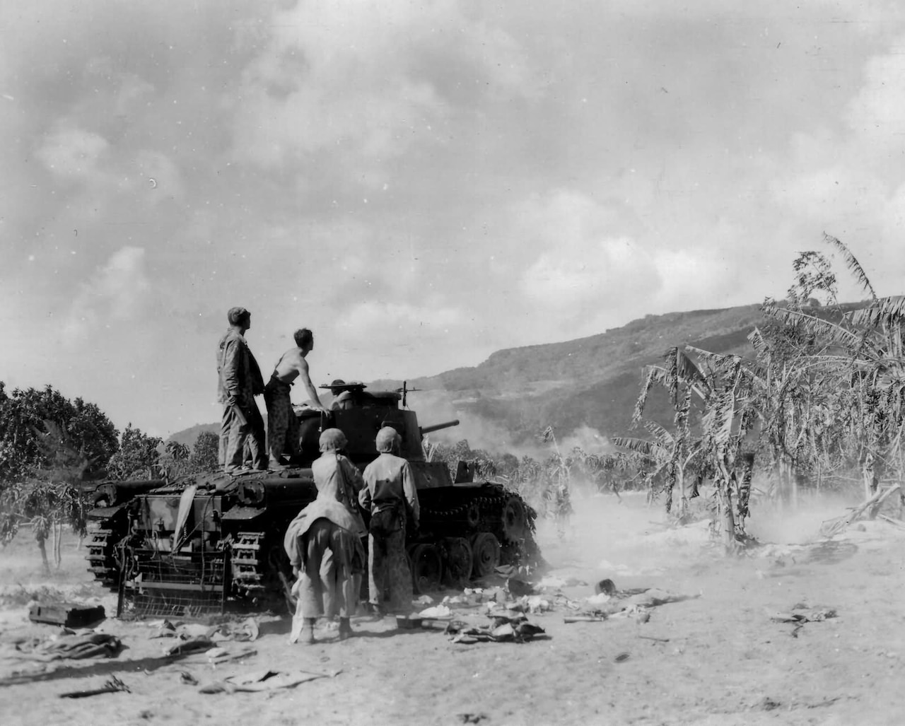 Five men stand on and around a captured Japanese World War II tank near palm trees and a mountain.
