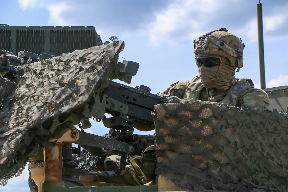 A soldier wearing a face mask looks through dark glasses from a military vehicle.