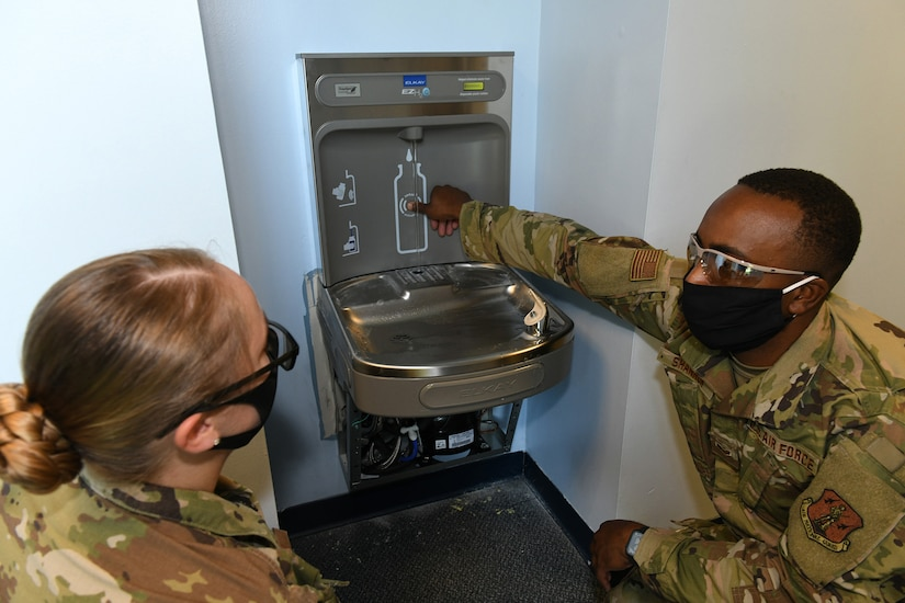 Photo shows two Airmen setting off a bottle sensor on a water fountain.