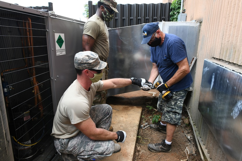 Photo shows two Airmen and a civilian working together on a HVAC unit outside.