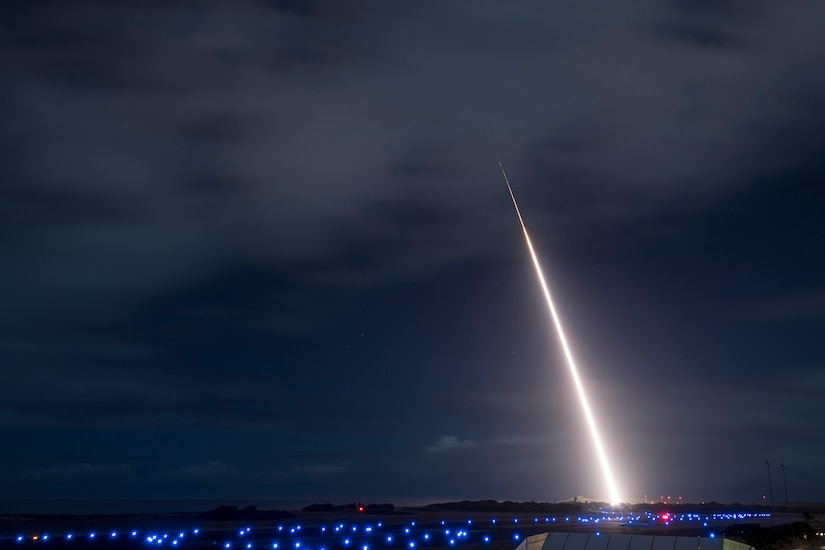 A rocket launches into a night sky.