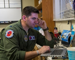 Capt. Steve Bichsel, 53rd Weather Reconnaissance Squadron navigator, types up a report, June 16, at St. Croix, U.S. Virgin Islands.  The Hurricane Hunters deployed to St. Croix to fly training missions over the Caribbean in preparation for the 2020 hurricane season. (U.S. Air Force photo by Tech. Sgt. Christopher Carranza)