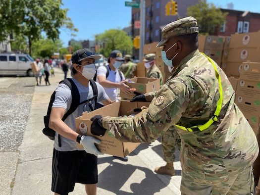 U.S. Army Pfc. Kristoffshakur Larmond, assigned to the 1st Battalion, 258th Field Artillery, part of the 27th Infantry Brigade Combat Team, distributes produce and canned goods in the Bushwick neighborhood of Brooklyn, N.Y., May 27, 2020. Troops have helped deliver more than 16 million meals to New Yorkers during the COVID-19 pandemic.